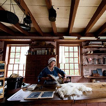 Store Clerk carding wool by hand.